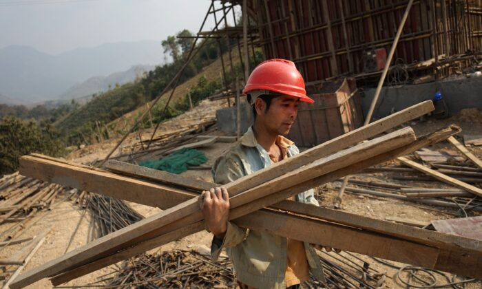 A Chinese worker carrying materials for the first rail line linking China to Laos, a key part of Beijing's 'Belt and Road' project across the Mekong, in Luang Prabang, on Feb. 8, 2020. (AIDAN JONES/AFP via Getty Images)